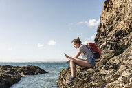 Young woman sitting on a rocky beach, using smartphone - UUF16463