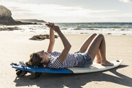 Young woman on the beach, relaxing on surfboard, using smartphone - UUF16475