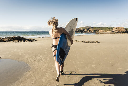 Young woman running on the beach, carrying surfboard - UUF16487