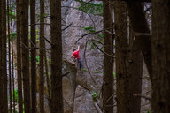Rock climber scaling rock face close to trees, Squamish, Canada - CUF46923