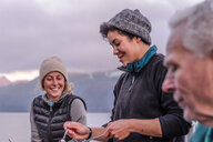 Friends having dinner by lakeside, Johnstone Strait, Telegraph Cove, Canada - CUF46947