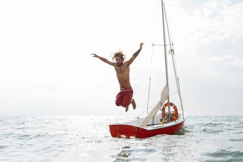Man jumping off sailboat - CUF46965