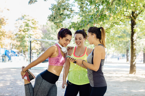 Friends exercising and using cellphone in park - CUF47001