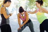 Friends exercising and using cellphone in park - CUF47004