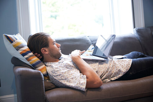 Man using laptop on sofa - CUF47070