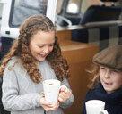Girls drinking hot chocolate beside camper van - CUF47076