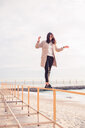 Woman walking on handrail at beach - CUF47079