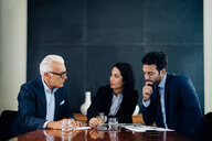 Businessmen and woman having discussion at boardroom table - CUF47100