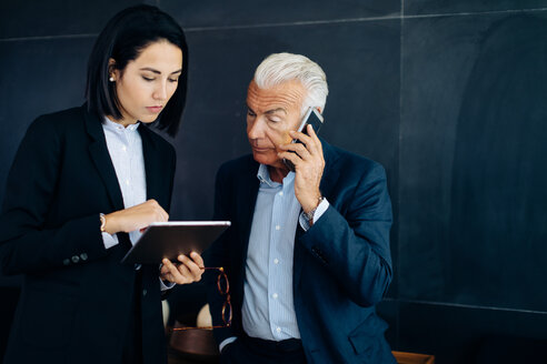 Businessman and woman looking at digital tablet and making smartphone call in boardroom - CUF47103