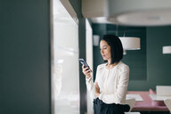 Young businesswoman in hotel looking at smartphone - CUF47109