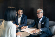 Two businessmen sitting in hotel table meeting with businesswoman - CUF47115