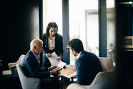 Businesswoman and men having meeting in hotel restaurant - CUF47118