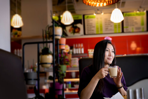 Mid adult woman holding coffee cup in cafe - CUF47127
