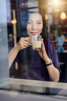 Mid adult woman with coffee looking out from cafe window seat, portrait - CUF47130