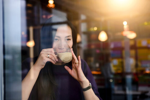 Mid adult woman drinking coffee in cafe window seat - CUF47136