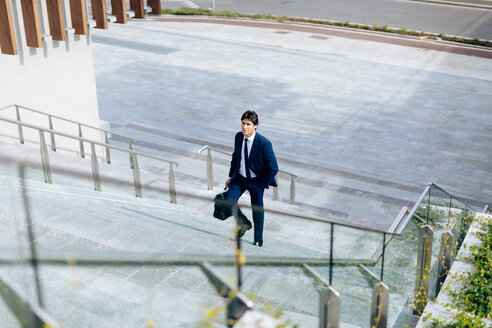 Businessman walking up stairway - CUF47151