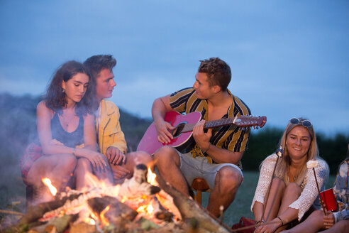Young man playing guitar at bonfire party in park - CUF47169