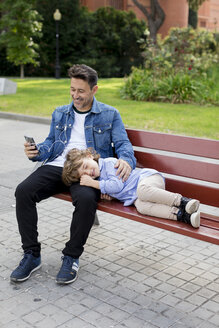 Happy father with son on a bench using cell phone and earbuds - MAUF02276