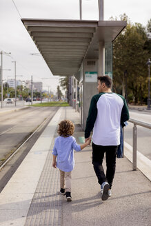 Rear view of father and son walking hand in hand at tram stop in the city - MAUF02279