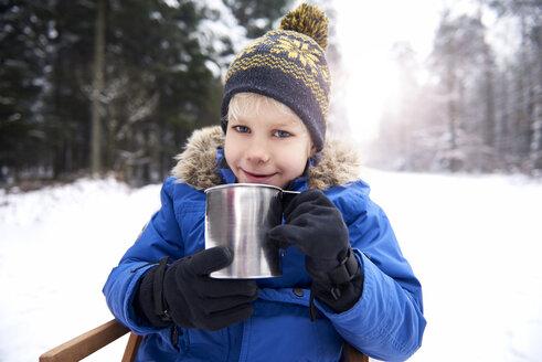 Portrait of smiling little boy sitting on sledge in winter forest drinking tea - ABIF01132