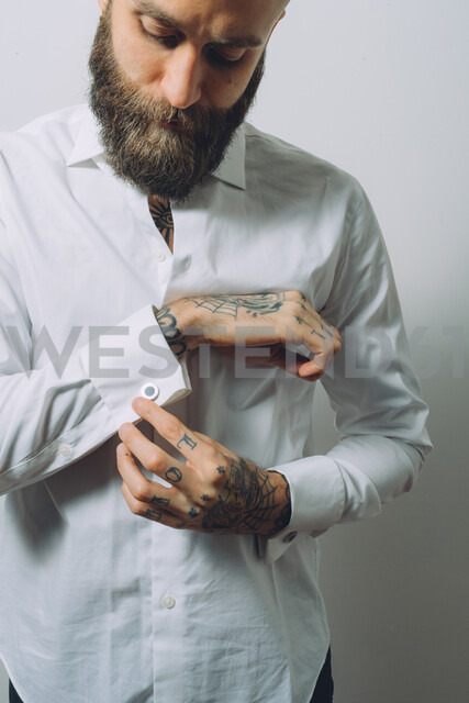 Bearded young man wearing white shirt, doing up cuff links, tattoos on hands - CUF47214