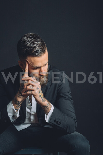 Young man wearing suit, sitting with worried expression, tattoos on hands - CUF47217