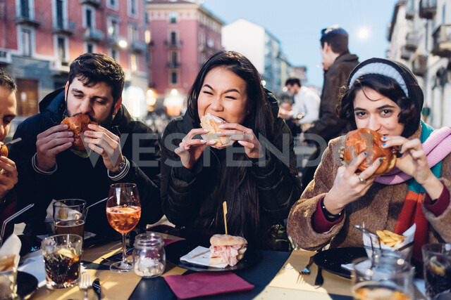 Friends enjoying burger at outdoor cafe, Milan, Italy - CUF47247 - Eugenio Marongiu/Westend61