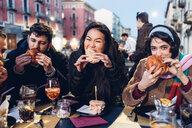 Friends enjoying burger at outdoor cafe, Milan, Italy - CUF47247