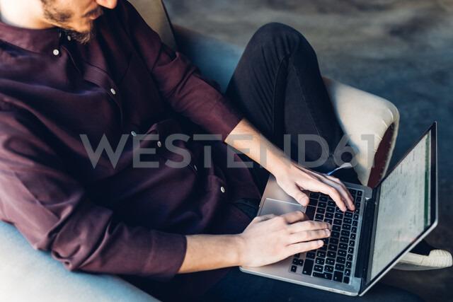 Man in armchair using laptop - CUF47256