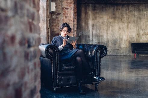 Woman in armchair using digital tablet - CUF47265