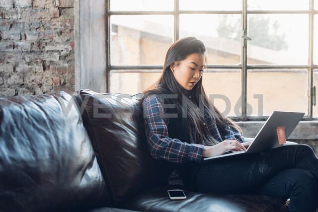 Woman on sofa by window using laptop - CUF47292