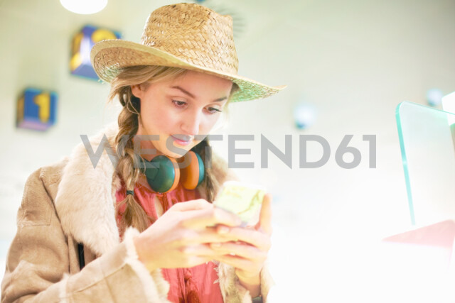 Young woman at airport, using smartphone, headphones around neck - CUF47301