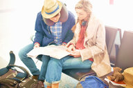 Young couple sitting in airport departure lounge, looking at map, planning trip - CUF47307