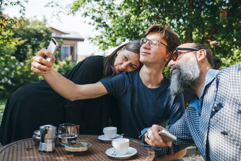 Family taking selfie over coffee in patio - CUF47343