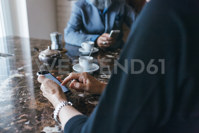 Couple using cellphone over coffee in kitchen - CUF47355