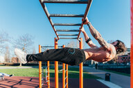 Man using horizontal ladder in outdoor gym - CUF47406