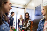 University students talking inside elevator - CUF47433