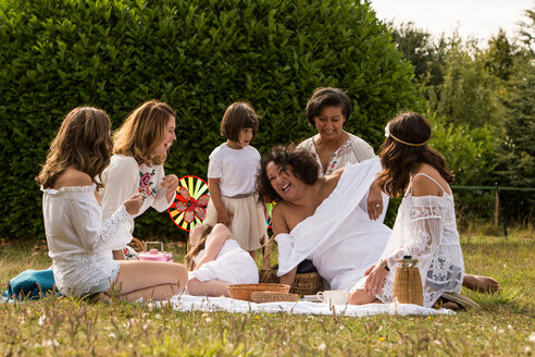 Female friends and family having picnic in garden - CUF47436