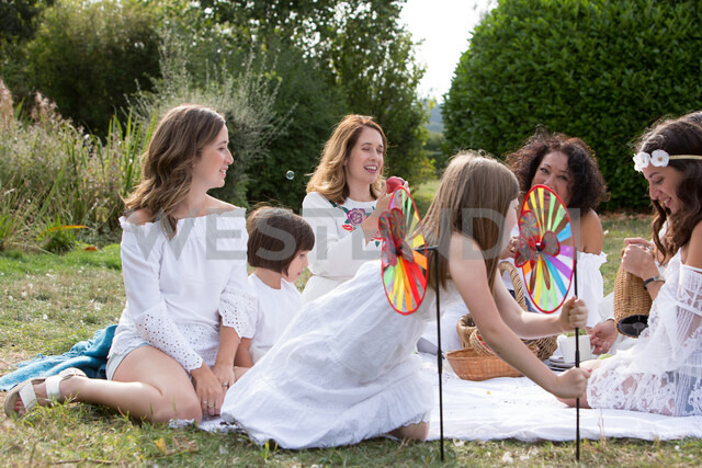 Female friends and family having picnic in garden - CUF47439