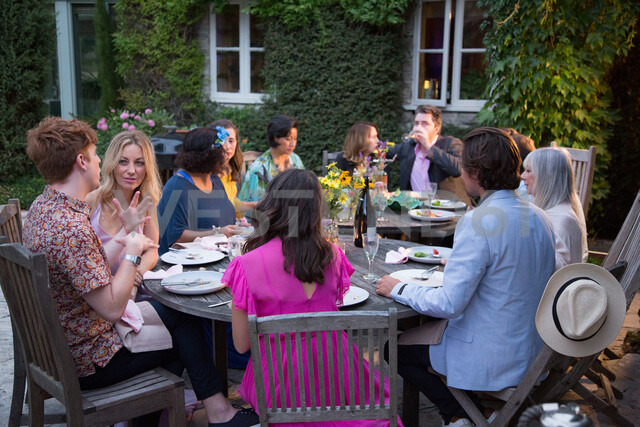 Guests enjoying and celebrating at garden party - CUF47448