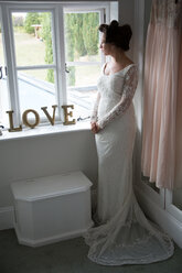 Bride looking out of window before wedding - CUF47454