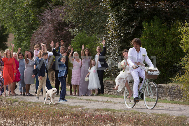 Wedding guests waving off newlyweds on bicycles - CUF47460