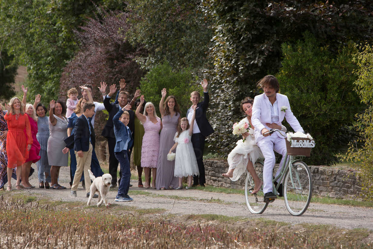 Wedding guests waving off newlyweds on bicycles - CUF47460 - Jim Forrest/Westend61