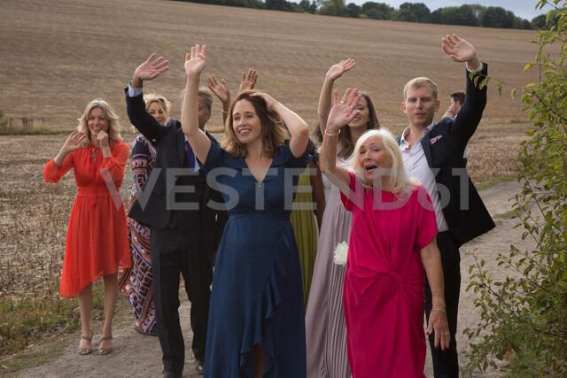 Wedding guests waving off newlyweds - CUF47463