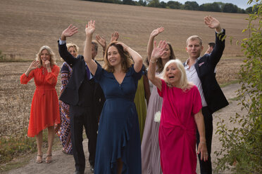Wedding guests waving off newlyweds - CUF47463