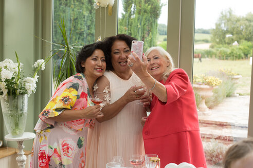 Wedding guests taking selfie at reception - CUF47469