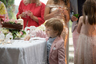 Boy curious about gifts and cake at wedding reception - CUF47475