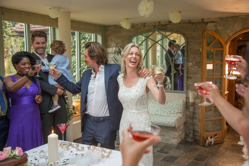 Wedding guests toasting to newlyweds at reception - CUF47478
