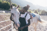Cool young man bonding with horse in rural equestrian arena - CUF47499