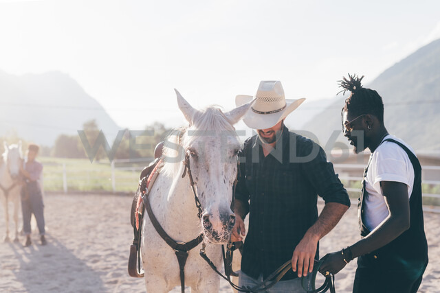 Cowboy handing horse's reins to young man in rural equestrian arena, Primaluna, Trentino-Alto Adige, Italy - CUF47502 - Eugenio Marongiu/Westend61